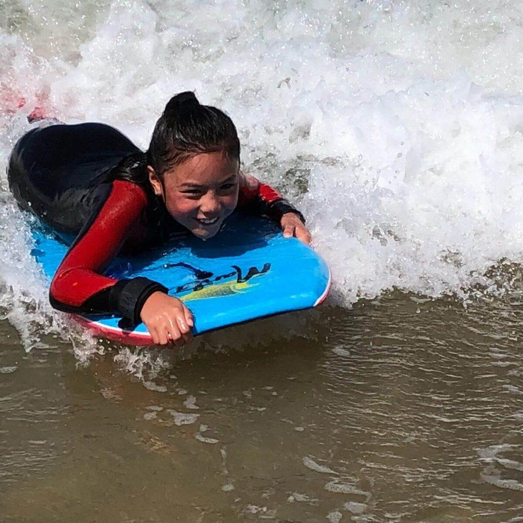 Girl in wetsuit bodyboarding
