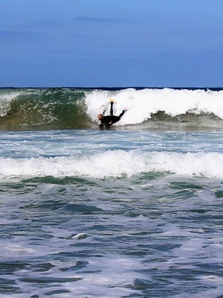Man catching a wave on a bodyboard