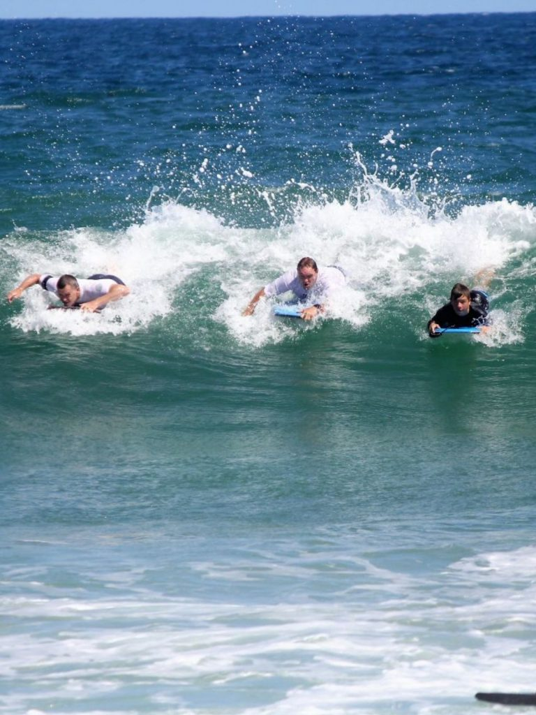 two men and a boy bodyboarding and catching a wave together