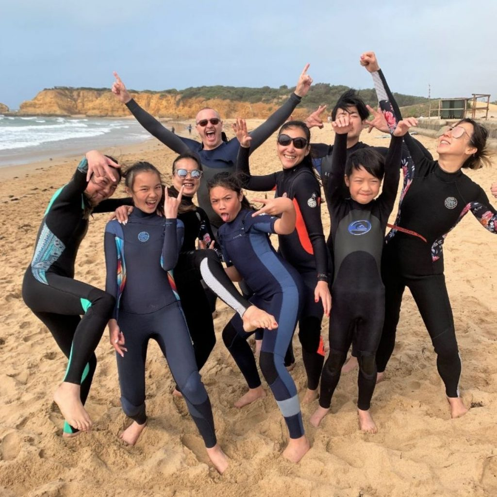 group of bodyboarders in wetsuits on the beach