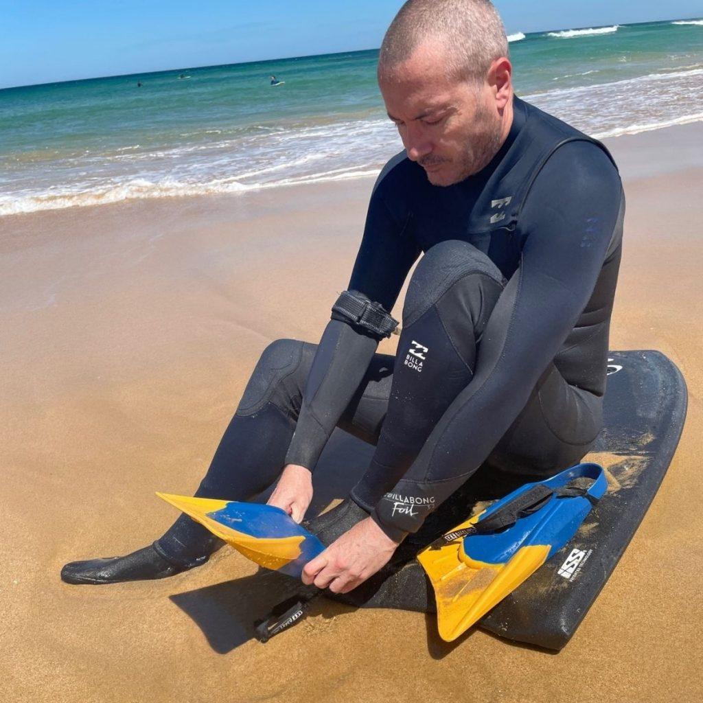 Man putting on bodyboard fins on the beach