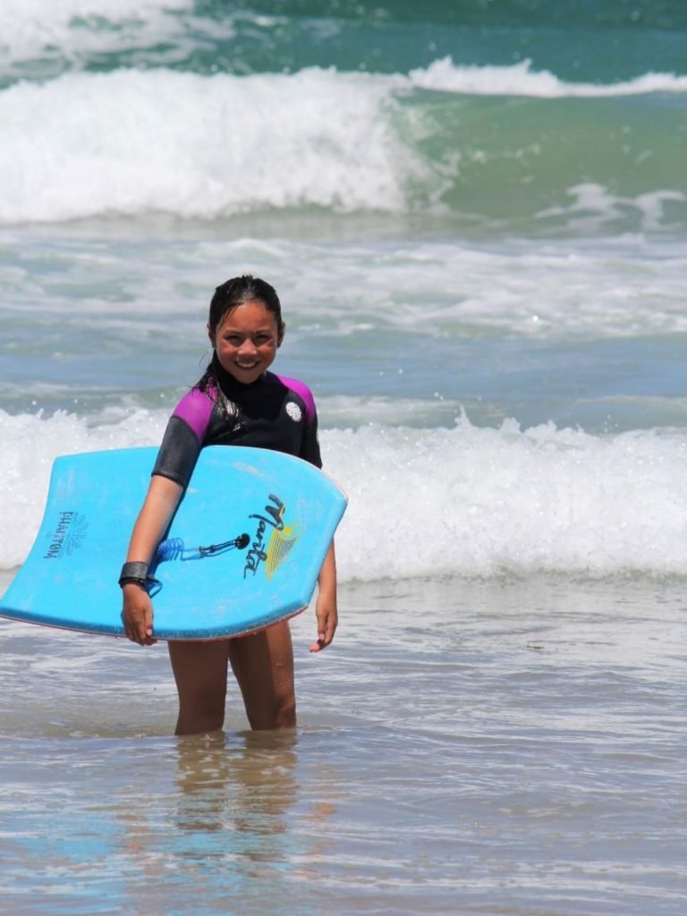 Young girl bodyboarding in the surf with bodyboard leash