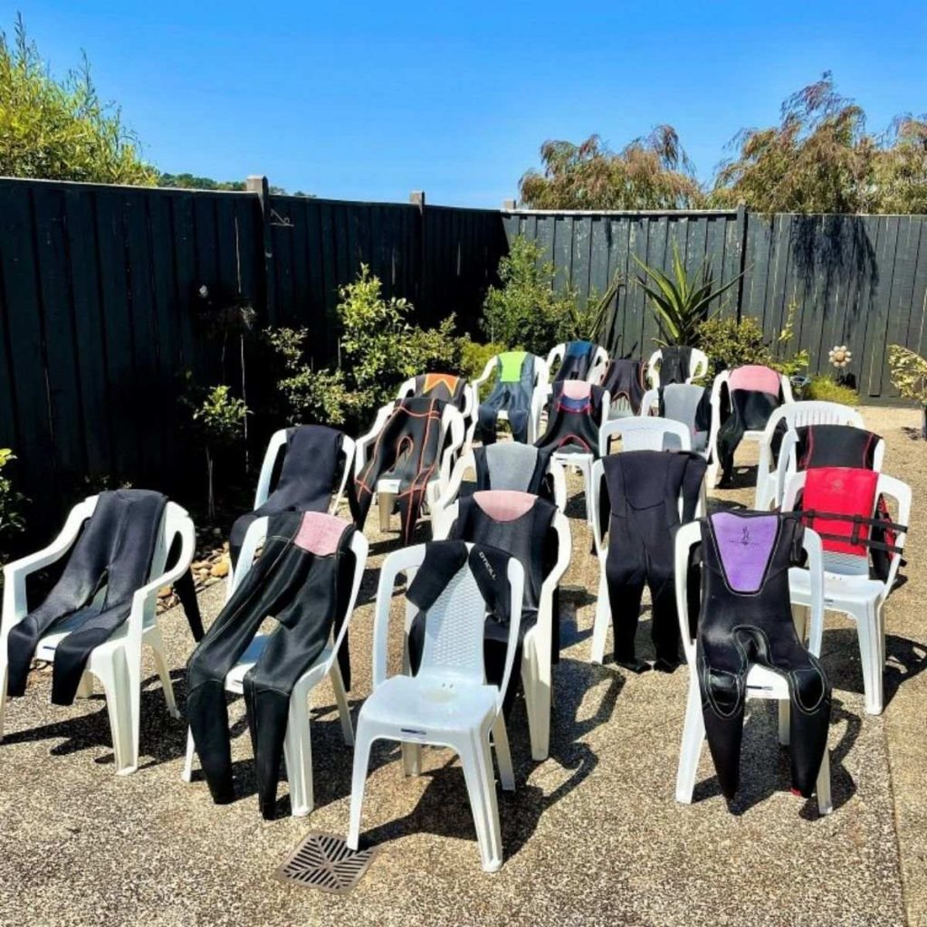 drying wetsuits on chairs on a sunny day