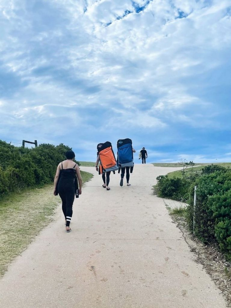 Walking to the beach with bodyboard bags