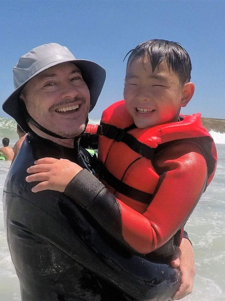 Man with boy in life vest in the ocean