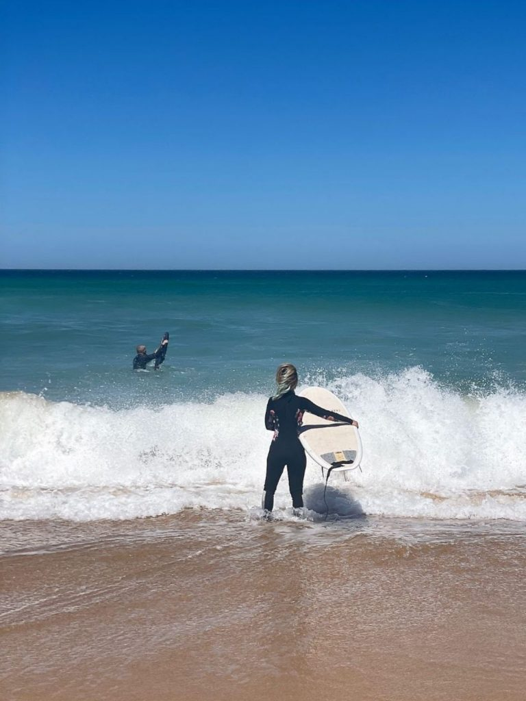 Woman surfing with male bodyboarder