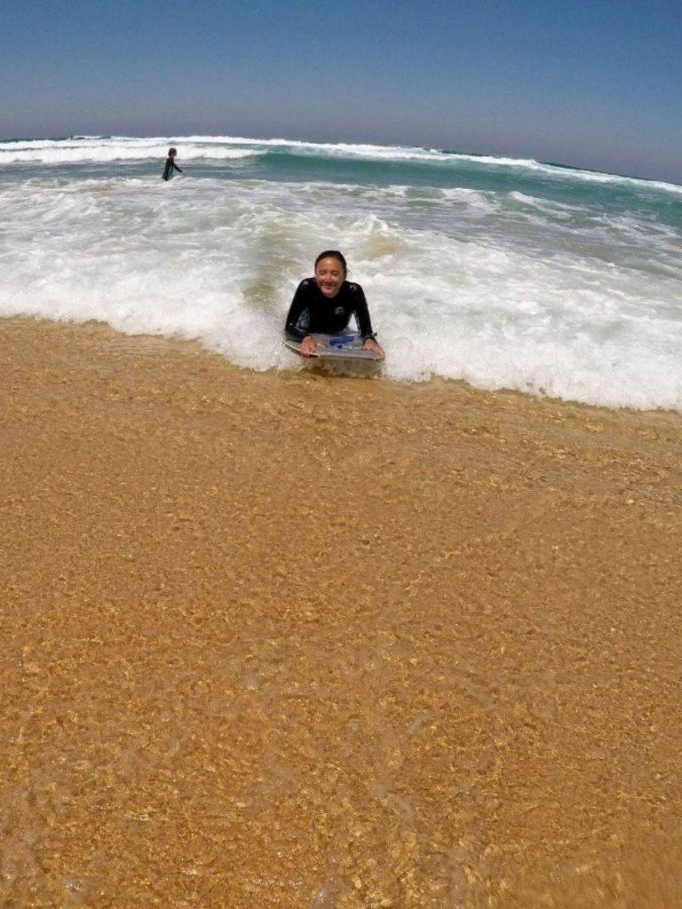 Woman bodyboarding to shore