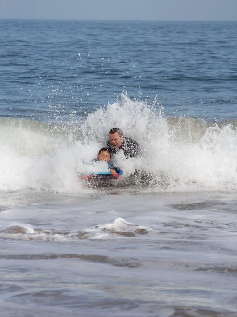 Father teaching daughter to catch broken wave while bodyboarding