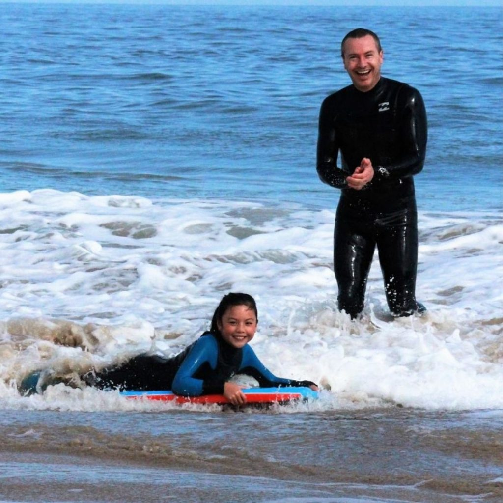 proud father watching daughter catch her first bodyboard wave