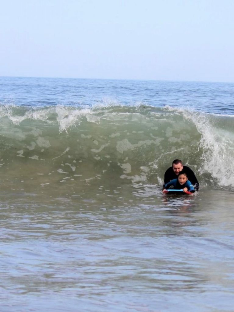 Father teaching daughter to catch unbroken wave while bodyboarding