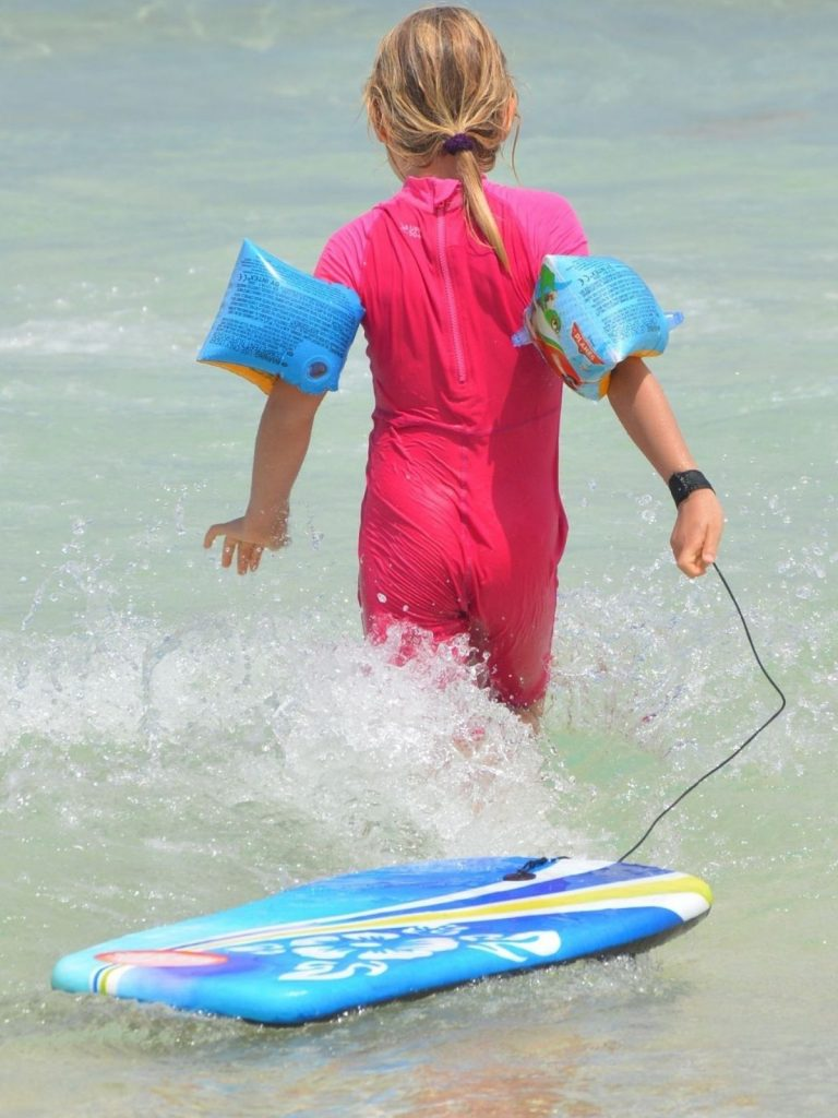 girl with arm floaties and pulling a bodyboard