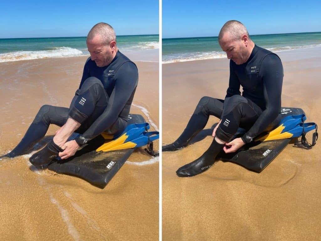 Putting on bodyboarding fin socks on the beach