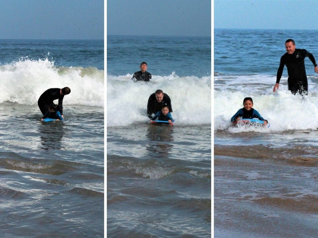 Father teaching daughter to catch a wave while bodyboarding