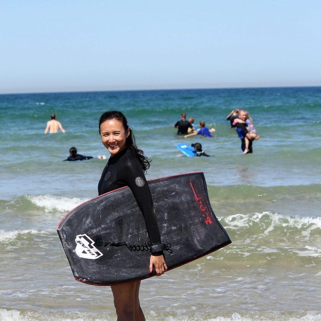 Woman on the beach going bodyboarding