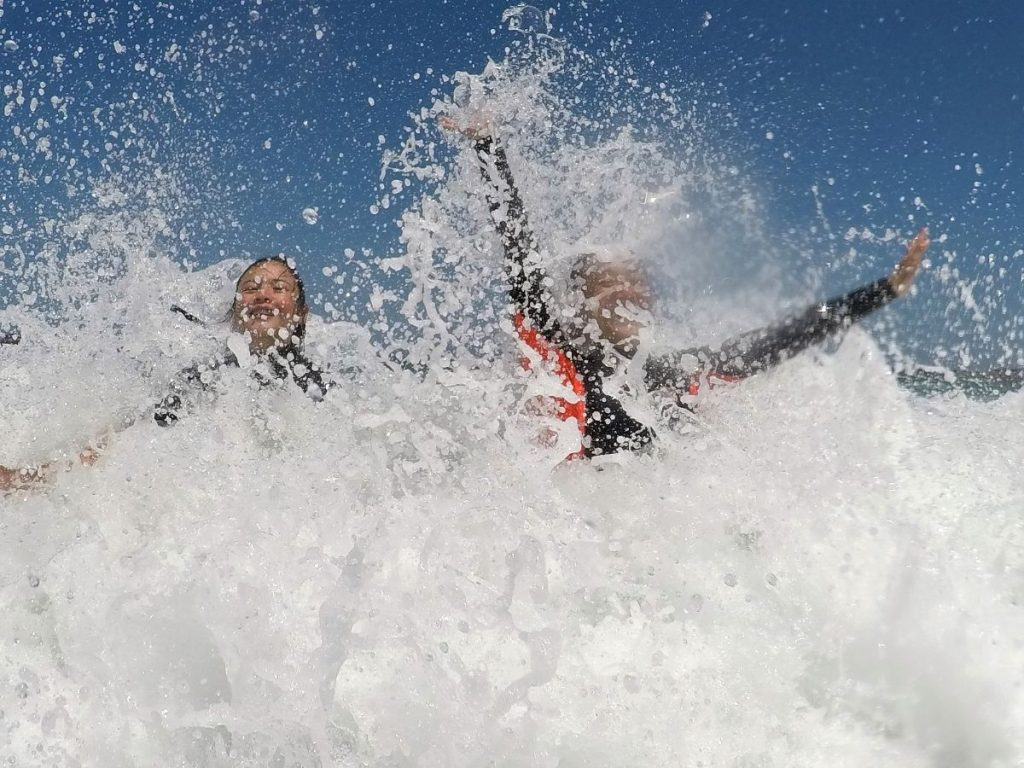 Family playing in the surf with wetsuits on