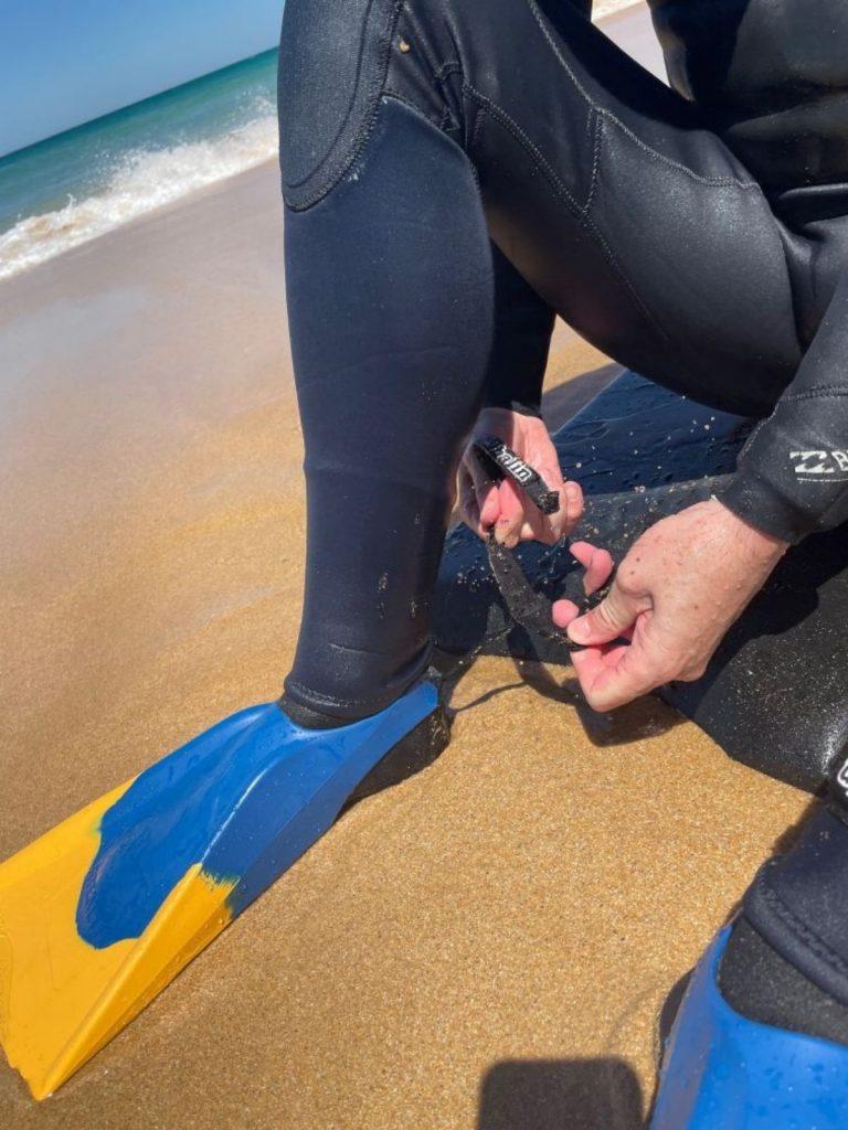 man wearing bodyboarding fins on the beach