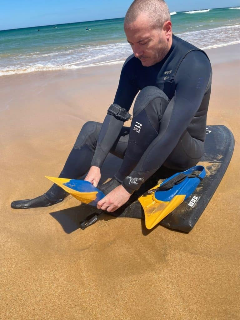 Putting on bodyboarding fins on the beach