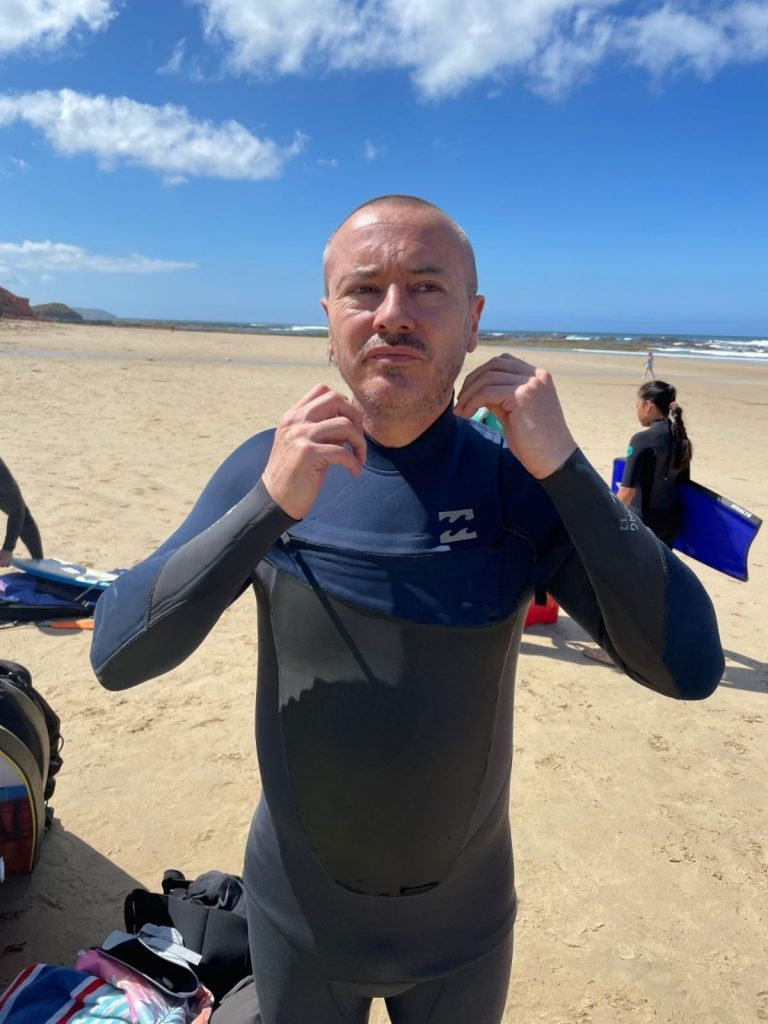 Man putting on his wetsuit