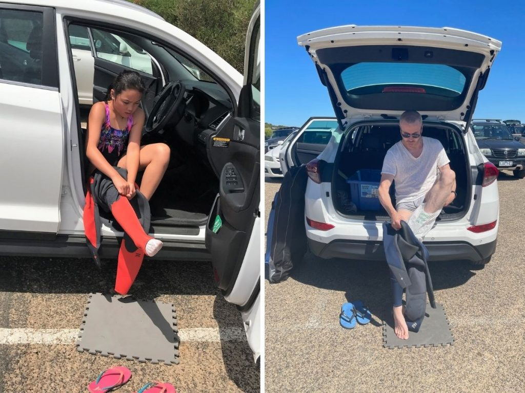 Father and daughter putting on wetsuits in the car