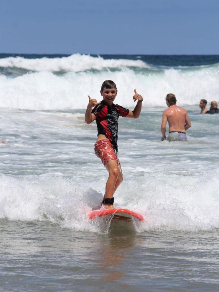 boy surfing with thumbs up
