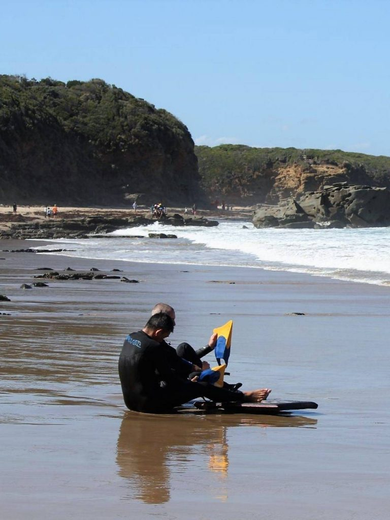 bodyboarders putting fins on by the beach